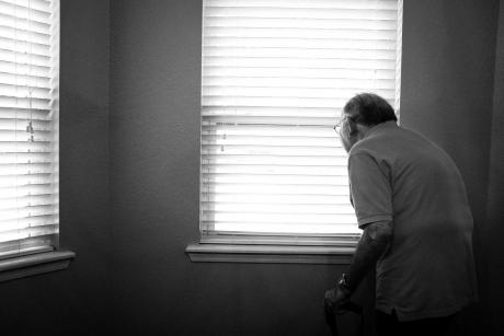 Black and white image of an older adult alone in a room, looking out the window