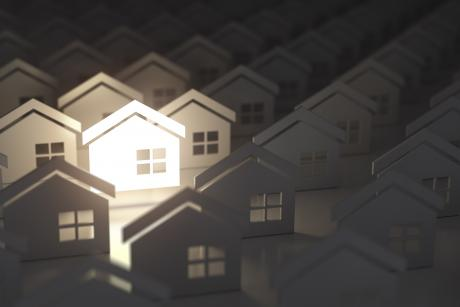 paper cutouts of housing with light shining on one