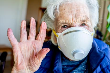 closeup of older woman wearing mask waving