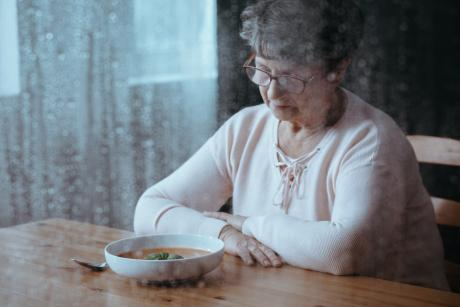 Older woman eating alone