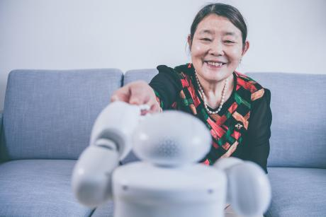 Older woman smiling at a robot