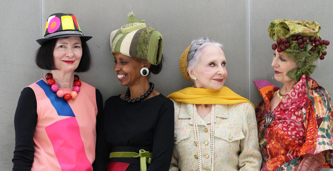 Group of 4 stylish, colorfully-dressed women smiling