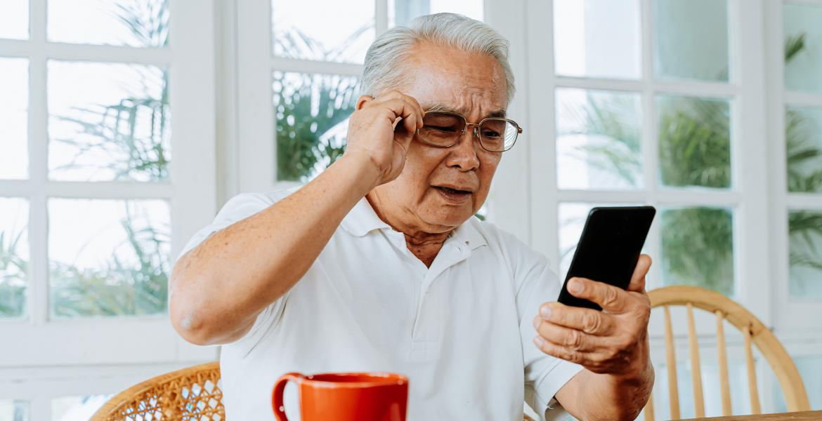 Older man having trouble seeing his phone
